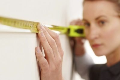 Closeup image of female worker using tape measure at work site