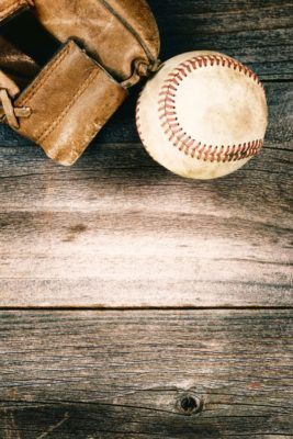 Vintage concept of an old baseball and weathered leather mitt on rustic wood. Format in vertical layout.